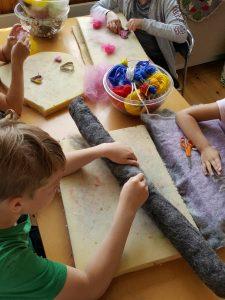 barn tovar en grå orm en hög med färgglada garner bredvid
