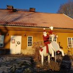 En jultomte vinkar från vit ren utanför Surahammars konst- och hantverksgille