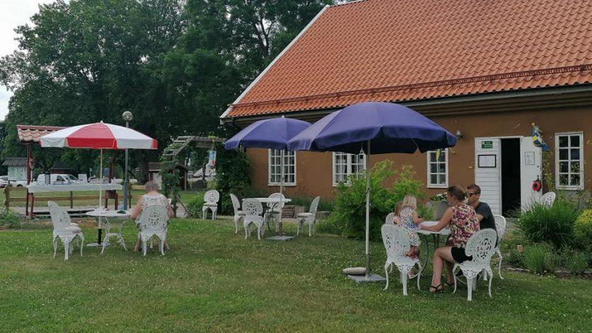 Stenhusets trädgård med marknadsstånd med kaffeservering, besökare sittandes vid vita trädgårdsbord och solskyddande parasoller