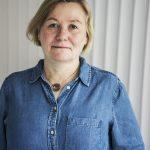 Agneta Carlson i denimskjorta framför vit strukturvägg.
