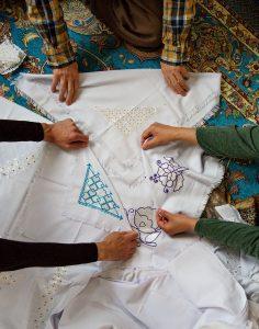 Händer som håller fram broderier från Afghanistan.