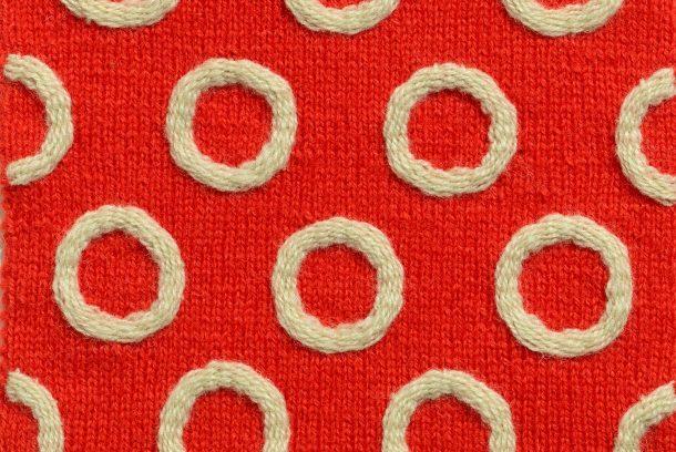 Röd stickad ruta med vita broderade ringar