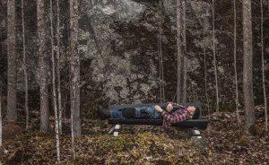 På en bänk i skogen ligger slöjdaren Jögge
