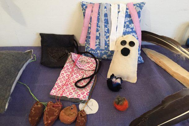 Föremål slöjdade av barn: två väskor, kudde, spöke och ett halsband av bark.