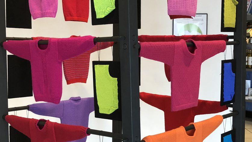 Utställning med stickade tröjor i starka rosa, röda. lila nyanser.