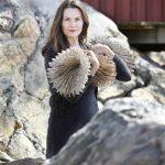 Porträtt av Isabelle Hällsjö vid klippor och röd sjöbod hållande en av sina skapelser.