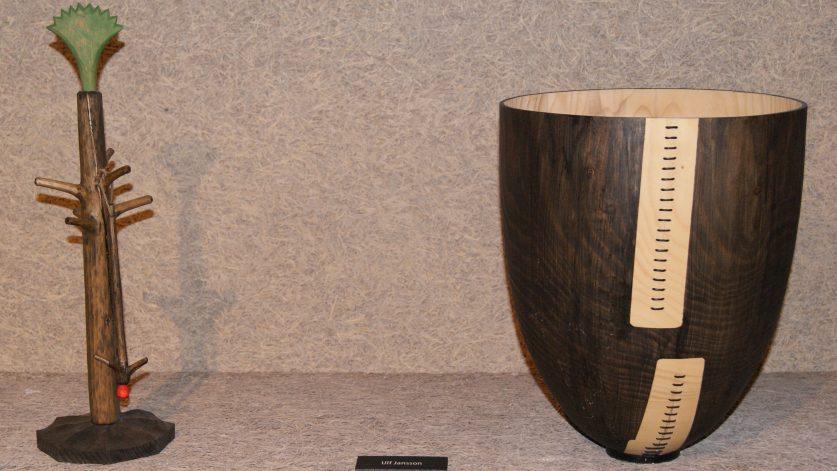 Två konstverk i trä: ett träd och en skål.