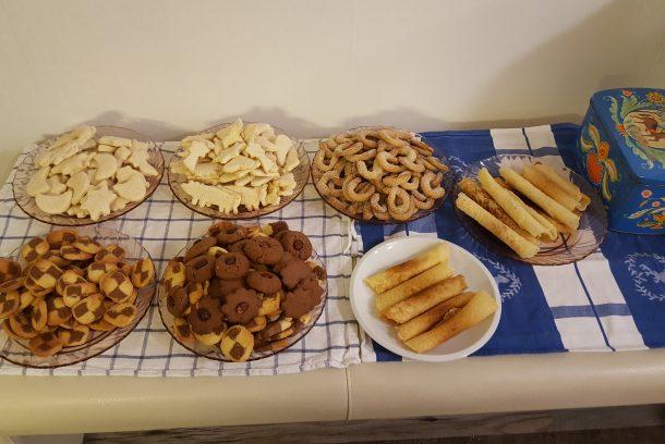 Sju sorters kakor på serveringsbord samt kakbruk i blått med häst på locket.