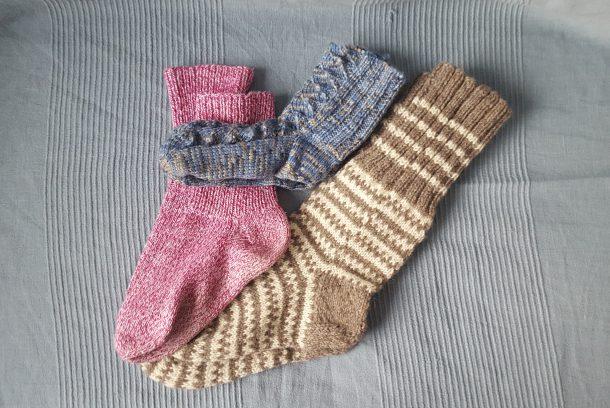 Tre par stickade sockor: röda, blå och bruna.