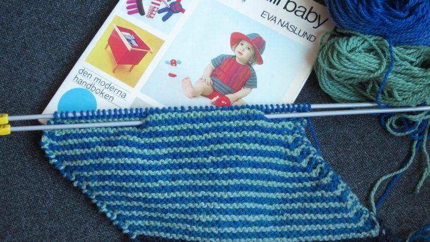 Bok om saker som går att göra själv till en baby med pågående handarbete i grönt och blått.