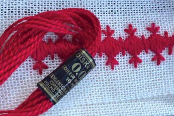 Rött garn och rött broderi mot vit bakgrund