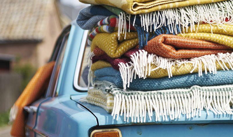 Blå Volvo med en stor hög färgglada filtar ovanpå bakluckan.