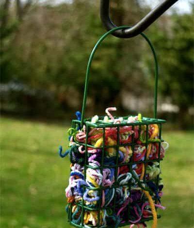 Garnrester i grön metallkorg som hänger på en krok i en grönskande trädgård