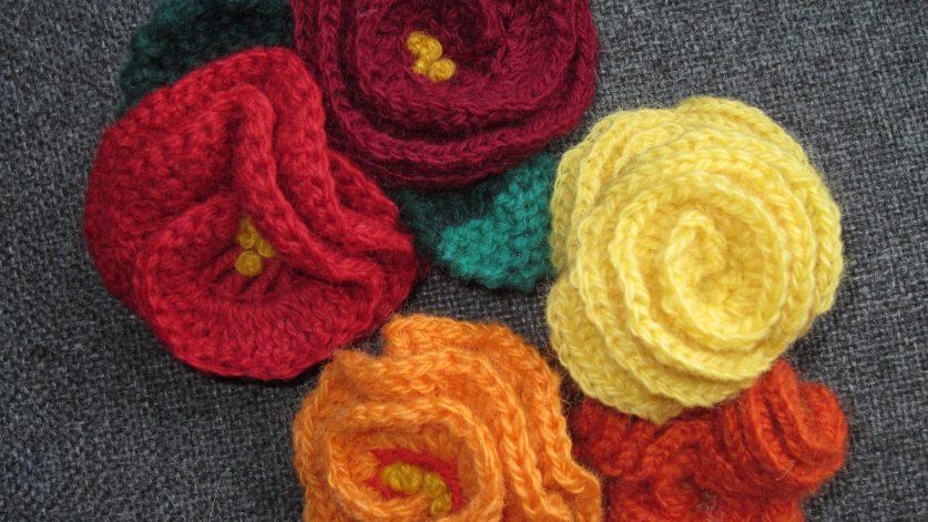 Fyra stickade hårspännen i form av röda, orange och gula rosor