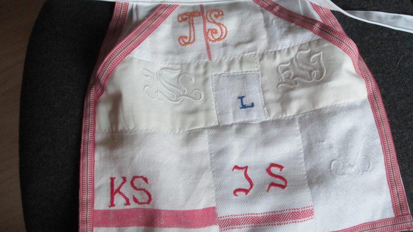 Litet förkläde i rött och vitt med olika initialer: JS, KS, L.