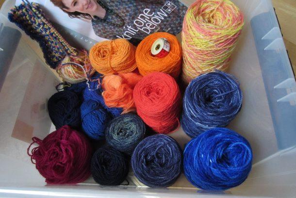 """Plastback med garner i olika färger samt boken """"knit one below""""."""