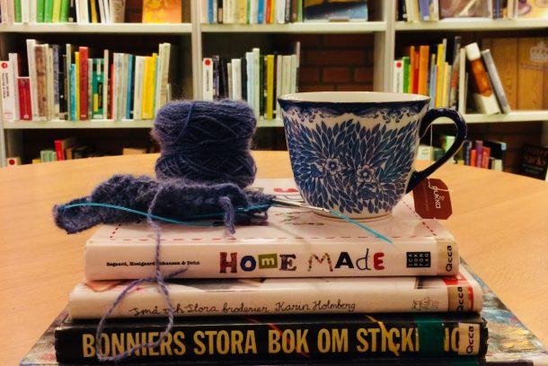 Mörklila garnnystan och blå, blomstermönstrad tekopp står på en hög med böcker, staplade på bord framför en bokhylla.