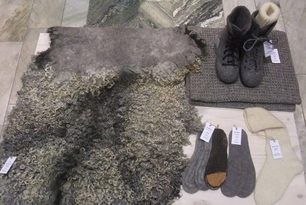 Fäll, kängor, strumpor och halsduk i ull utlagda på marmorgolv.