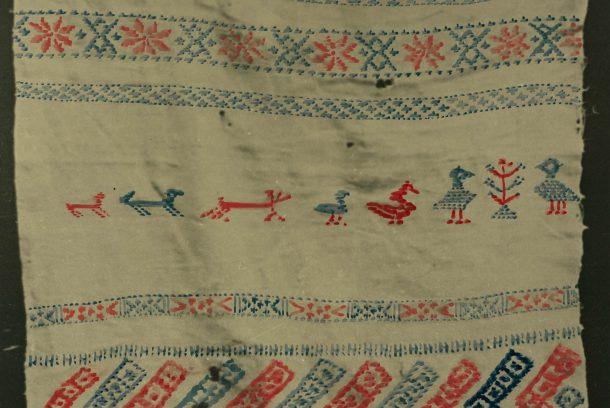 Ett stycke linne i rött, blått och vitt med djurmotiv.