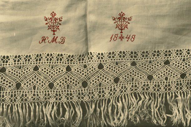 Närbild på flätade fransar med emblemet HMD och daterad 1848.