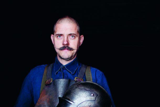 Mustaschprydde Albert Collins, smed av rustningar i garvat skinnförkläde och rustningshjälm framför bröstet.