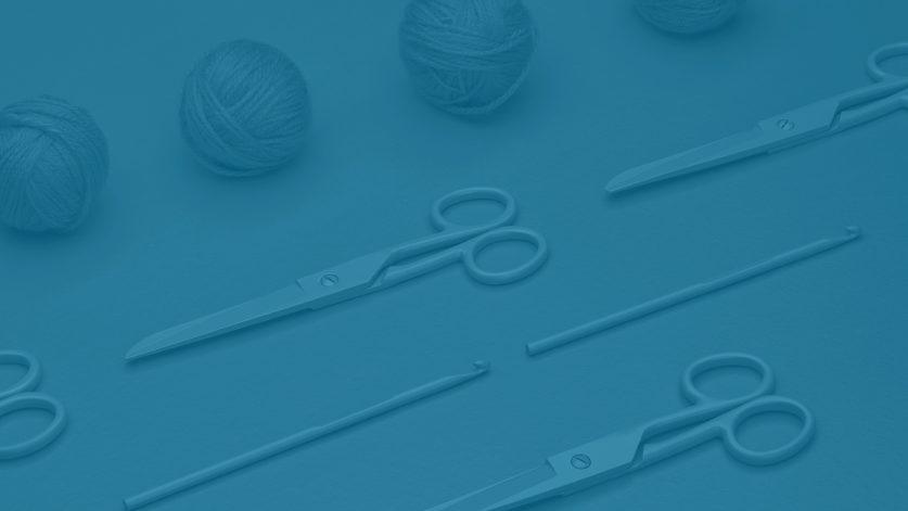 Blå bild med saxar, virknålar och garnnystan