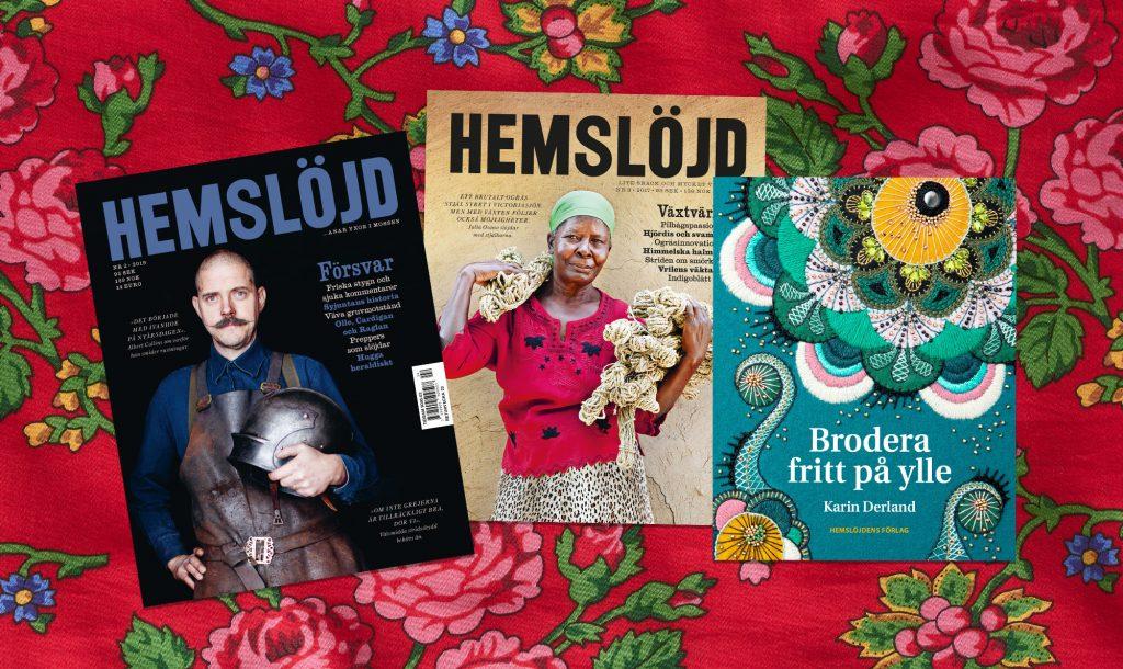 """Två utgåvor av tidningen Hemslöjd och boken """"Brodera på Ylle"""" på blommig duk."""