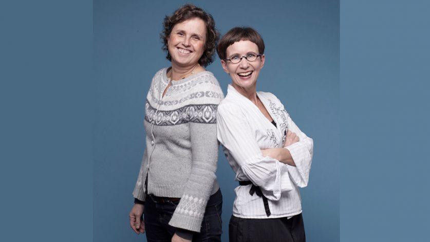 Spillmaterialets drottningar Lill O- Sjögren och Maria Zeilon från Skryta slow design poserar framför blå bakgrund.