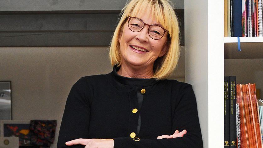 Åse Berglund lutad mot vit bokhylla.