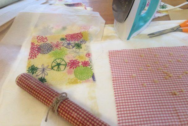 Blommigt och röd-vit rutigt tunt tyg med bivax på, duk till inslagning/förvaring av mat under tillverkning och en färdig bivaxduk på rulle
