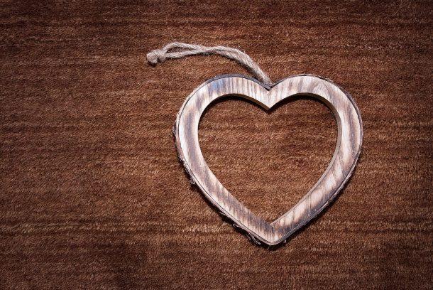 Hjärta i trä mot brun bakgrund.
