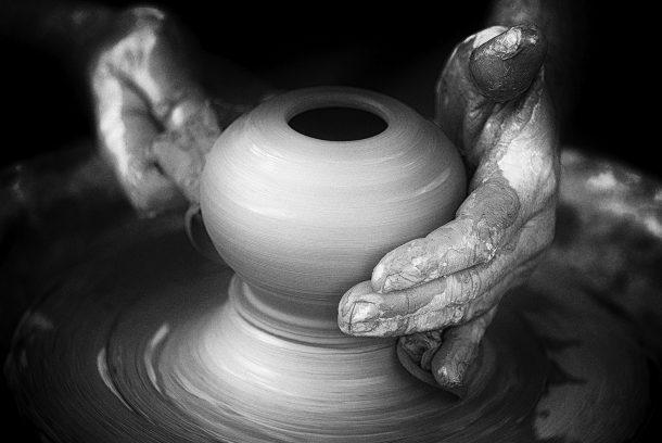 Svartvit bild av händer som drejar lera