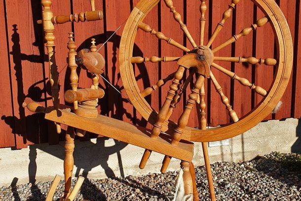 spinnrock och kardor framför en faluröd trävägg